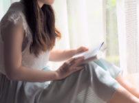 窓際で本を読んでいる女性